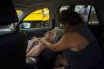 Virginia Mosvold, 84, leans back in a car seat as her daughter Sissel comforts her after they were rescued from their home on Ol' Freetown Farm that was flooded by Hurricane Dorian, before being taken to the hospital, on the outskirts of Freeport, Bahamas, Wednesday, Sept. 4, 2019. Rescue crews in the Bahamas fanned out across a blasted landscape of smashed and flooded homes trying to reach drenched and stunned victims of Hurricane Dorian and take the full measure of the disaster. (AP Photo/Ramon Espinosa)