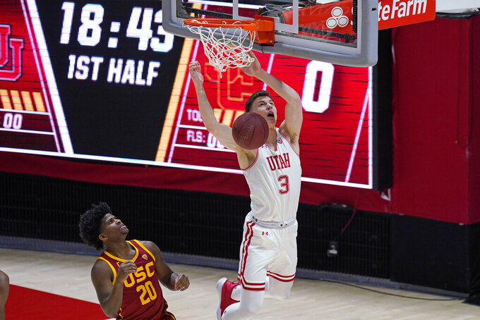 Utah guard Pelle Larsson (3) dunks as Southern California guard Ethan Anderson (20) defends during the first half of an NCAA college basketball game Saturday, Feb. 27, 2021, in Salt Lake City. (AP Photo/Rick Bowmer)