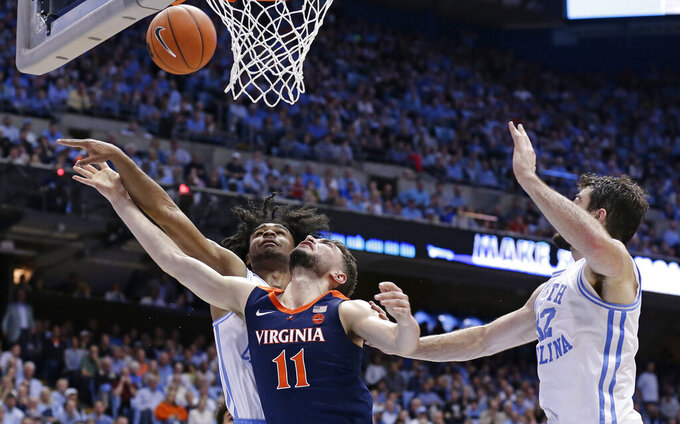 North Carolina's Coby White, left, and Luke Maye guard while Virginia's Ty Jerome (11) shoots during the second half of an NCAA college basketball game in Chapel Hill, N.C., Monday, Feb. 11, 2019. (AP Photo/Gerry Broome)