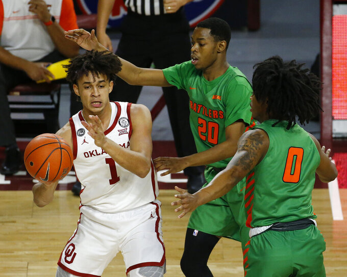 Oklahoma's Jalen Hill (1) passes the ball away from Florida A&M's Jai Clark (20) and Jahvon Smith (0) during the first half of an NCAA college basketball game in Norman, Okla., Saturday, Dec. 12, 2020. (AP Photo/Garett Fisbeck)