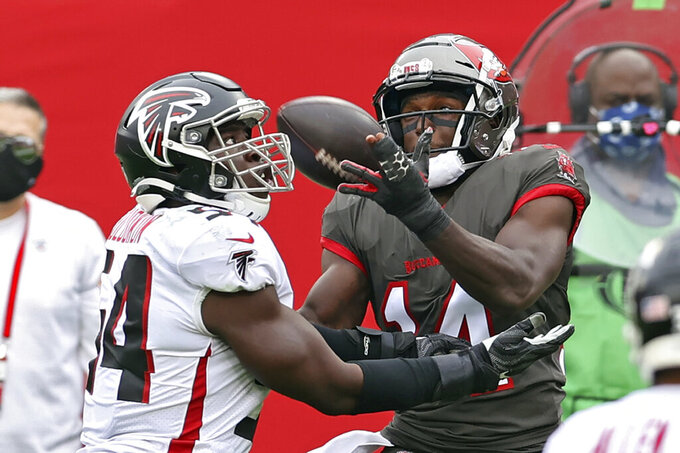 Tampa Bay Buccaneers wide receiver Chris Godwin (14) pulls in a 7-yard touchdown reception in front of Atlanta Falcons linebacker Foye Oluokun (54) during the first half of an NFL football game Sunday, Jan. 3, 2021, in Tampa, Fla. (AP Photo/Mark LoMoglio)