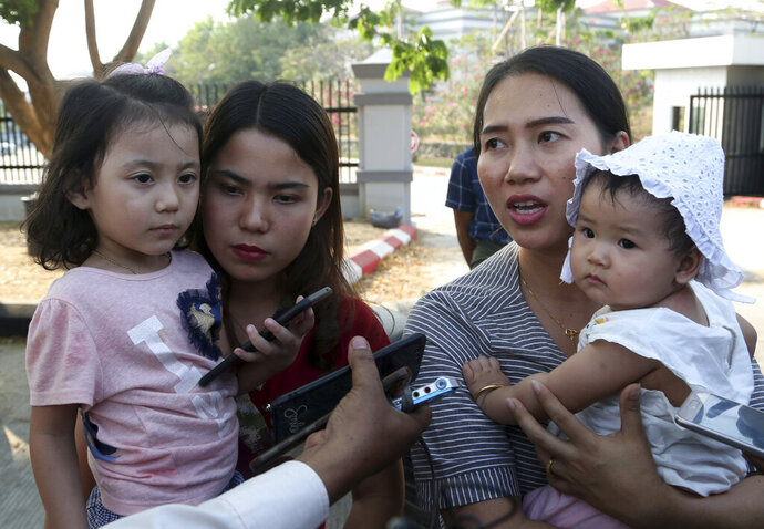 Chit Su Win, wife of Reuters journalist Kyaw Soe Oo, left, and Pan Ei Mon, right, wife of Reuters journalist Wa Lone, hold their children as they leave the Supreme Court after hearing an appeal of the two journalists in Naypyitaw, Myanmar, Tuesday, March 26, 2019. Myanmar's Supreme Court agreed Tuesday to rule on an appeal filed by lawyers for two Reuters journalists sentenced to seven years in prison for their reporting on Myanmar's brutal crackdown on Rohingya Muslims. (AP Photo/Aung Shine Oo)