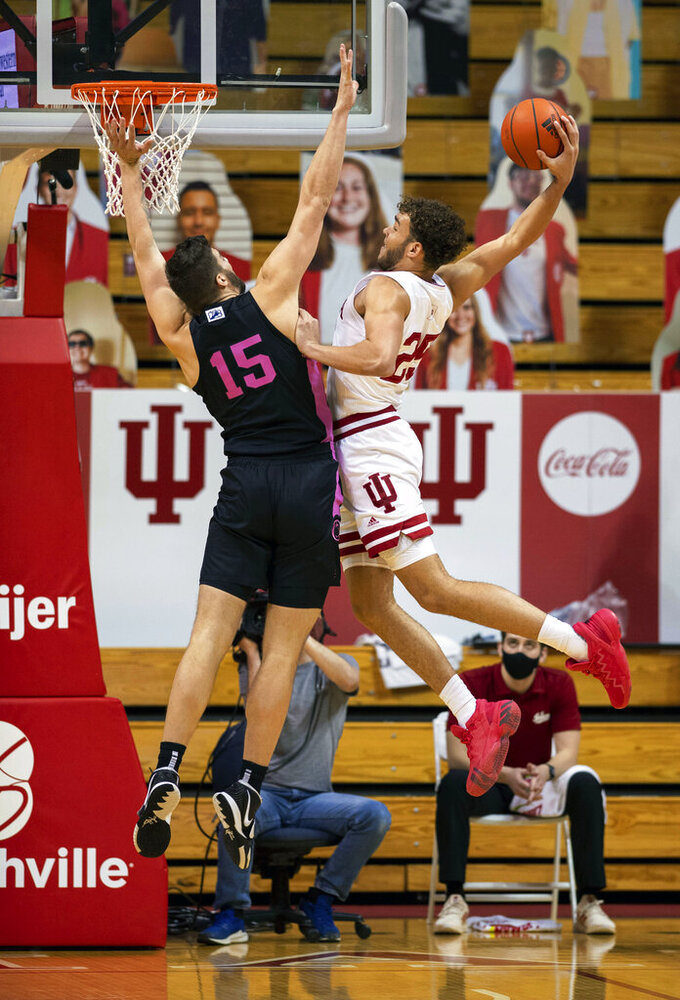 Indiana forward Race Thompson (25) is defended by Penn State forward Trent Buttrick (15) as he tries to score with a slam dunk during the first half of an NCAA college basketball game, Wednesday, Dec. 30, 2020, in Bloomington, Ind. (AP Photo/Doug McSchooler)