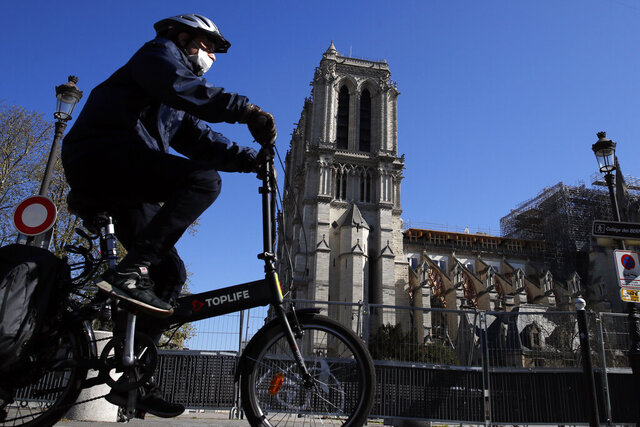 A man wearing a face mask rides his bike in front of Notre Dame cathedral during a nationwide confinement to counter the Covid-19, in Paris, Sunday, April 5, 2020. The new coronavirus causes mild or moderate symptoms for most people, but for some, especially older adults and people with existing health problems, it can cause more severe illness or death. (AP Photo/Christophe Ena)