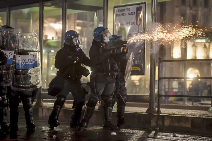 Riot Police fire tear gas as clashes broke out during a protest against the government restriction measures to curb the spread of COVID-19 in Turin, Italy, Monday, Oct. 26, 2020. Italy's leader has imposed at least a month of new restrictions to fight rising coronavirus infections, shutting down gyms, pools and movie theaters and putting an early curfew on cafes and restaurants. (Claudio Furlan/LaPresse via AP)