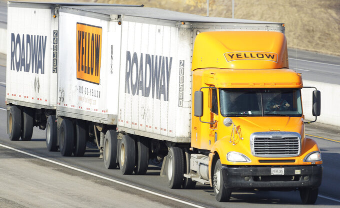 FILE - In this Feb. 2, 2010, file photo, a Yellow Freight/Roadway Express truck travels east on I-70, near Lecompton, Kan. Congressional watchdogs are questioning the government's decision to award a $700 million coronavirus relief loan to a struggling trucking company on grounds its operations are critical for maintaining national security. YRC Worldwide provides transportation and logistics services, such as delivering food, electronics and other supplies to military locations around the country. (AP Photo/Orlin Wagner, File)