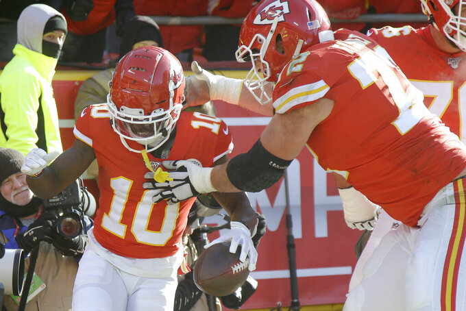 Kansas City Chiefs' Tyreek Hill (10) celebrates his touchdown run with offensive tackle Eric Fisher (72) during the first half of the NFL AFC Championship football game against the Tennessee Titans Sunday, Jan. 19, 2020, in Kansas City, MO. (AP Photo/Charlie Riedel)