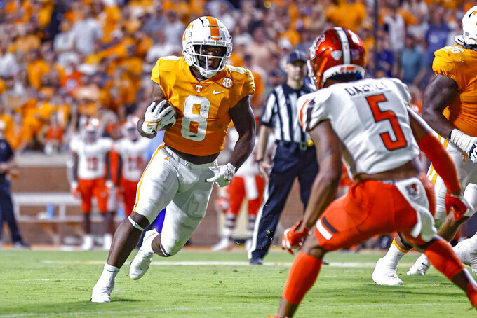 Tennessee running back Tiyon Evans (8) carries as Bowling Green safety Sy Dabney (5) defends during the second half of an NCAA college football game Thursday, Sept. 2, 2021, in Knoxville, Tenn. (AP Photo/Wade Payne)