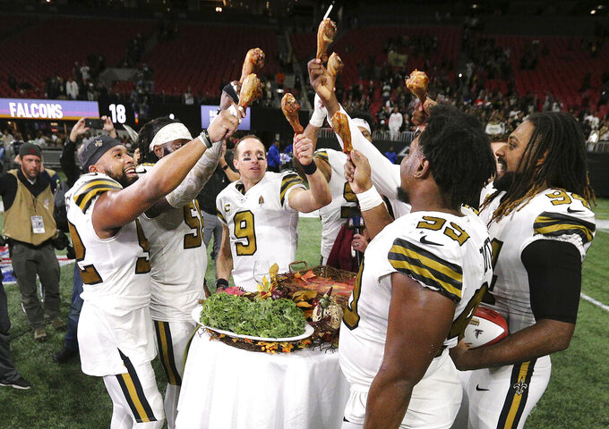 New Orleans Saints quarterback Drew Brees and teammates celebrate a 26-18 victory over the Atlanta Falcons with turkey legs on Thanksgiving Day, after an NFL football game Thursday, Nov. 28, 2019, in Atlanta. The Falcons clinched the NFC South title. (Curtis Compton/Atlanta Journal-Constitution via AP)