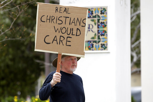 Andrew Goetze holds a sign in opposition to a Palm Sunday service taking place at Godspeak Calvary Chapel Sunday, April 5, 2020, in Newbury Park, Calif. Many churches, beaches, parks and hiking trails around the state have been closed because they attracted large crowds amid the coronavirus outbreak. (AP Photo/Marcio Jose Sanchez)