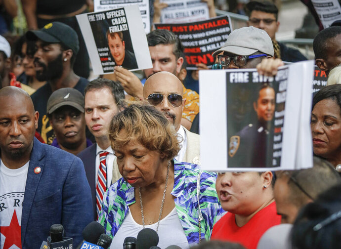 Gwen Carr, center, the mother of chokehold victim Eric Garner, listens during a news conference as Loyda Colon, co-director of the Justice Committee, call for charging other officers involved in the death of Garner, after NYPD Commissioner James O'Neill announced his decision to fire NYPD officer Daniel Pantaleo for the 2014 death of Garner, Monday Aug. 19, 2019, in New York. (AP Photo/Bebeto Matthews)