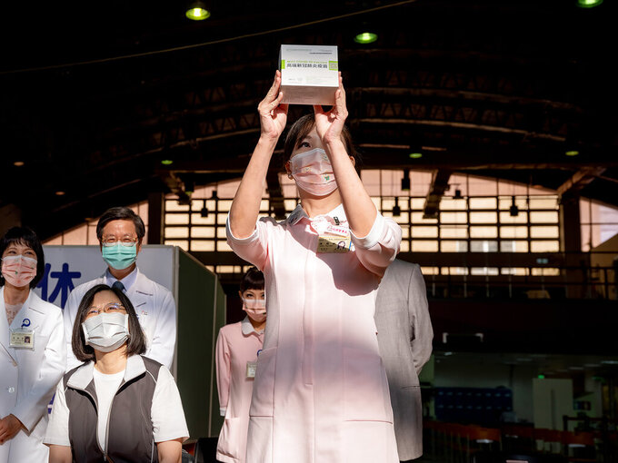 In this photo released by the Taiwan Presidential Office, a nurse holds up the packaging for the first domestically developed coronavirus vaccine made by Medigen Vaccine Biologics Corp. as Taiwanese President Tsai Ing-wen, front left, prepares to be inoculated at the Taiwan University Hospital in Taipei, Taiwan on Monday, Aug. 23, 2021. The vaccine was given emergency approval by regulators in July using a shortcut that prompted fierce opposition from parts of Taiwan's medical and scientific community. (Taiwan Presidential Office via AP)