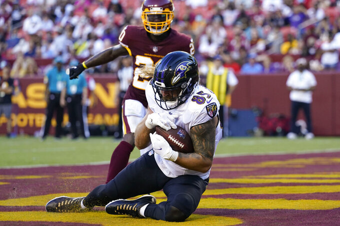 Baltimore Ravens tight end Eric Tomlinson (85) making a touchdown catch against Washington Football Team cornerback Jimmy Moreland (20) during the first half of a preseason NFL football game, Saturday, Aug. 28, 2021, in Landover, Md. (AP Photo/Carolyn Kaster)