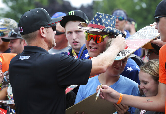 Clint Bowyer (14) signs autographs as he arrives for the driver/crew chief meeting prior to the NASCAR Cup series auto race at Watkins Glen International, Sunday, Aug. 4, 2019, in Watkins Glen, N.Y. (AP Photo/John Munson)