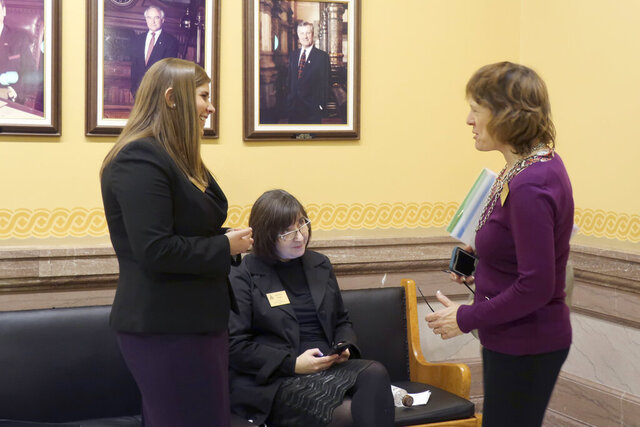 Anti-abortion lobbyists from left, Brittany Jones, of the Family Policy Alliance of Kansas; Jeannette Pryor, of the Kansas Catholic Conference, and Jeanne Gawdun, of Kansans for Life, confer outside the state Senate chamber ahead of a debate on a proposed constitutional amendment on abortion, Wednesday, Jan. 29. 2020, at the Statehouse in Topeka, Kansas. The amendment would overturn a Kansas Supreme Court decision protecting abortion rights. (AP Photo/John Hanna)