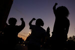FILE - In this June 23, 2020, file photo, people raise their fists in Kansas City, Mo., during a protest over the death of Black people at the hands of police. (AP Photo/Charlie Riedel, File)