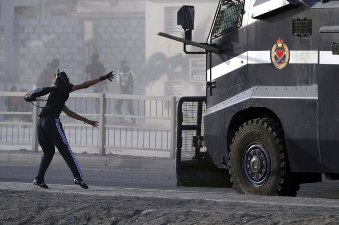 File - In this Friday, March 15, 2013 file photo, a Bahraini anti-government protester throws a piece of wood at an armored police vehicle during clashes in Jidhafs, Bahrain. A decade ago, against all odds, a popular uprising convulsed the monarchy of Bahrain as a wave of revolutionary protests swept across the Middle East. But after a brutal crackdown and years of escalating repression, activists say the small kingdom is less free now than even before the Arab Spring, as authorities crush hopes for political reform. (AP Photo/Hasan Jamali, File)