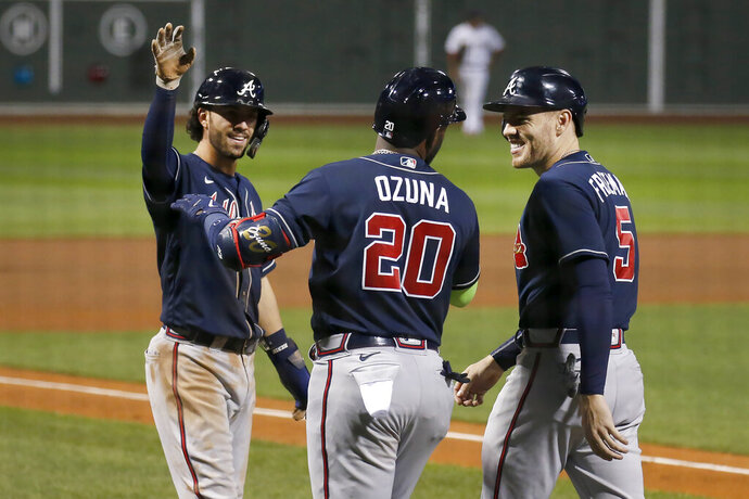 Atlanta Braves' Marcell Ozuna (20) celebrates with teammates Dansby Swanson, left, and Freddie Freeman (5) after they all scored on Ozuna's three-run home run during the eighth inning of a baseball game against the Boston Red Sox, Tuesday, Sept. 1, 2020, in Boston. (AP Photo/Mary Schwalm)