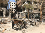 Men load a carpet and mattress on to a bicycle in front of damaged buildings in the town of Douma, the site of a suspected chemical weapons attack, near Damascus, Syria, Monday, April 16, 2018. Faisal Mekdad, Syria's deputy foreign minister, said on Monday that his country is
