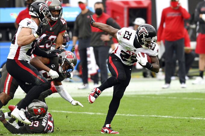 Atlanta Falcons running back Brian Hill (23) breaks away from the Tampa Bay Buccaneers on a rush during the second half of an NFL football game Sunday, Jan. 3, 2021, in Tampa, Fla. (AP Photo/Jason Behnken)