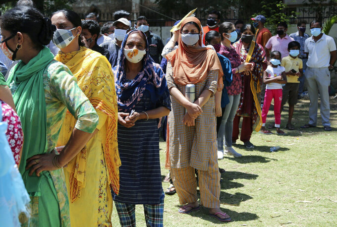 People line up to get tested for COVID-19 in Jammu, India, Monday, May 24, 2021. India crossed another grim milestone Monday of more than 300,000 people lost to the coronavirus as a devastating surge of infections appeared to be easing in big cities but was swamping the poorer countryside. (AP Photo/Channi Anand)