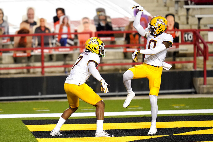 Minnesota wide receiver Rashod Bateman (0) celebrates after wide receiver Chris Autman-Bell (7) caught a touchdown pass during the second half of an NCAA college football game against Maryland, Friday, Oct. 30, 2020, in College Park, Md. (AP Photo/Julio Cortez)