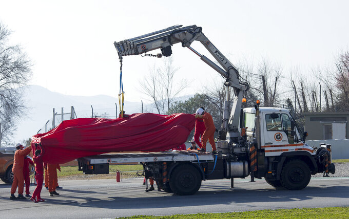 Scuderia Ferrari Mission Winnow's Sebastian Vettel's car is lifted by a crane during the Formula One pre-season testing session at the Barcelona Catalunya racetrack in Montmelo, outside Barcelona, Spain, Friday, Feb. 21, 2020. (AP Photo/Joan Monfort)