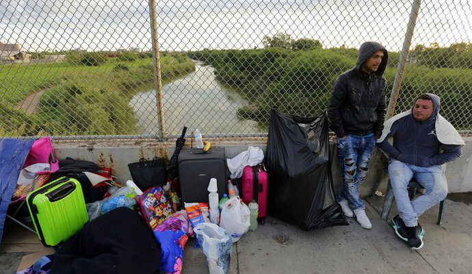 FILE - In this Nov. 2, 2018, file photo, Yenly Morales,left, and Yenly Herrera, right, immigrants from Cuba seeking asylum in the United States, wait on the Brownsville and Matamoros International Bridge in Matamoros, Mexico. The U.S. government will expand its policy requiring asylum seekers to wait outside the country in one of Mexico's most dangerous cities. According to officials for two congressional Democrats, the Department of Homeland Security says it will implement its