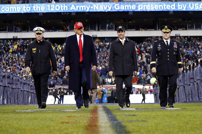 President Donald Trump and Secretary of Defense Mark Esper cross the field after the first half of an NCAA college football game between Army and Navy, Saturday, Dec. 14, 2019, in Philadelphia. (AP Photo/Jacquelyn Martin)
