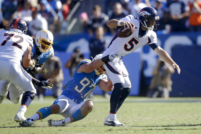 Denver Broncos quarterback Joe Flacco is tackled by Los Angeles Chargers defensive end Joey Bosa during the second half of an NFL football game Sunday, Oct. 6, 2019, in Carson, Calif. (AP Photo/Marcio Jose Sanchez)