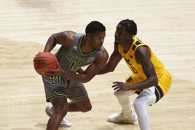 Baylor guard Jared Butler, left, is defended by West Virginia guard Kedrian Johnson, right, during the first half of an NCAA college basketball game Tuesday, March 2, 2021, in Morgantown, W.Va. (AP Photo/Kathleen Batten)