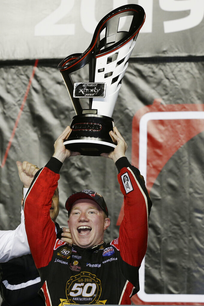 Tyler Reddick holds his trophy in Victory Lane after winning the NASCAR Xfinity Series auto racing championship on Saturday, Nov. 16, 2019, at Homestead-Miami Speedway in Homestead, Fla. (AP Photo/Terry Renna)