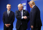 NATO Secretary General Jens Stoltenberg, left, and British Prime Minister Boris Johnson, center, greet U.S. President Donald Trump during official arrivals at a NATO leaders meeting at The Grove hotel and resort in Watford, Hertfordshire, England, Wednesday, Dec. 4, 2019. NATO Secretary-General Jens Stoltenberg rejected Wednesday French criticism that the military alliance is suffering from brain death, and insisted that the organization is adapting to modern challenges. (Peter Nicholls, Pool Photo via AP)