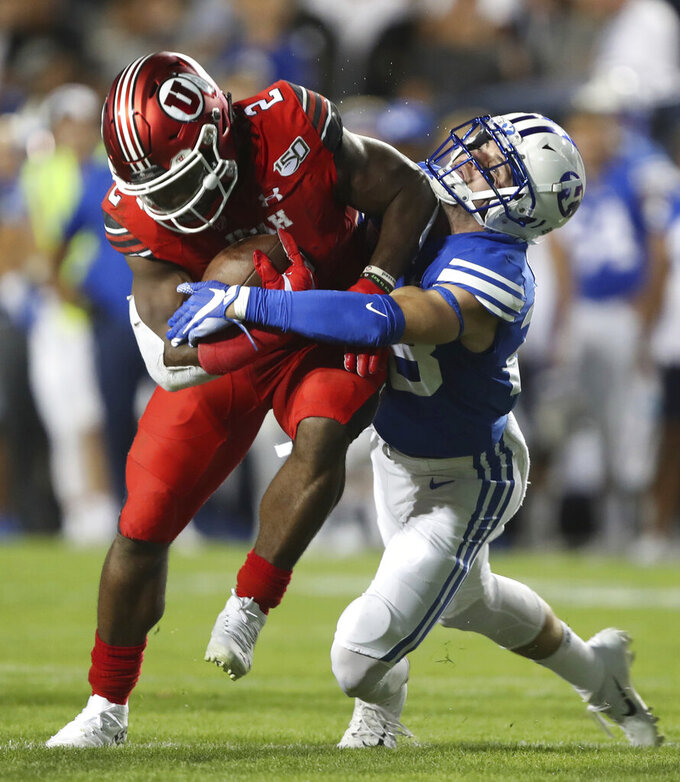 BYU defensive back Sawyer Powell (28) tries to take down Utah running back Zack Moss (2) in the first half during an NCAA college football game, Thursday, Aug. 29, 2019, in Provo, Utah. (AP Photo/George Frey)