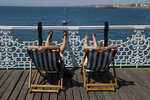 Two people relax in deck chairs as beachgoers enjoy the sunshine and sea on what is now Britain's hottest day of the year so far, in Brighton, England, Friday, July 31, 2020. Temperatures have reached 35C (95F) at London's Heathrow Airport. (AP Photo/Alastair Grant)