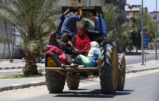 Palestinian family sit in a truck as they fleeing their house in Gaza City, Tuesday, May 18, 2021. Since the fighting began last week, the Israeli military has launched hundreds of airstrikes it says are targeting Hamas' militant infrastructure, while Palestinian militants have fired thousands of rockets into Israel. (AP Photo/Hatem Moussa)