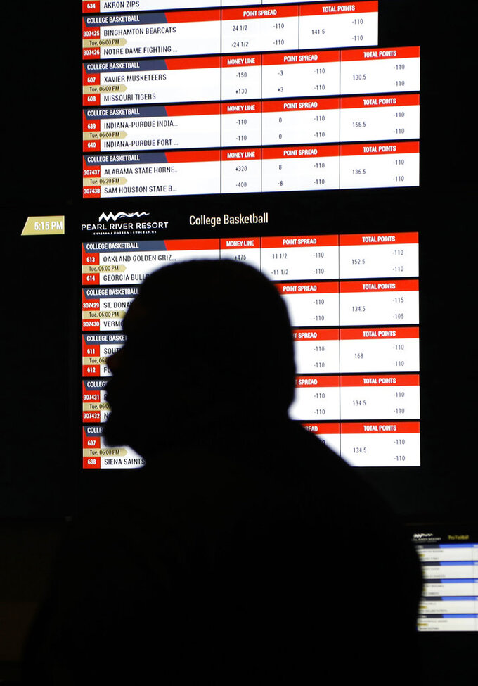 In this Dec. 18, 2018 photo, a person walks by a betting wall at the Pearl River Resort in Philadelphia, Miss. The sports book owned by the Mississippi Band of Choctaw Indians is the first to open on tribal lands outside of Nevada following a U.S. Supreme Court ruling earlier this year, a no-brainer business decision given the sports fans among its gambling clientele. (AP Photo/Rogelio V. Solis)