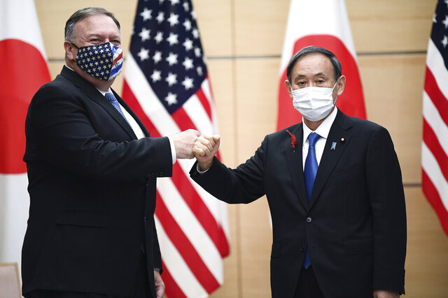 Japan's Prime Minister Yoshihide Suga, right, and U.S. Secretary of State Mike Pompeo, left, greet prior to their meeting at the prime minister's office in Tokyo, Tuesday, Oct. 6, 2020, ahead of the four Indo-Pacific nations' foreign ministers meeting. (Charly Triballeau/Pool Photo via AP)