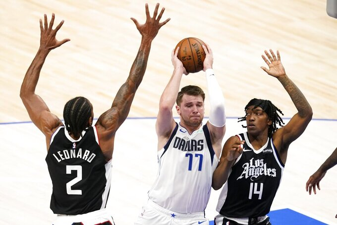 Los Angeles Clippers' Kawhi Leonard (2) and Terance Mann (14) defend as Dallas Mavericks guard Luka Doncic (77) drives to the basket in the first half in Game 4 of an NBA basketball first-round playoff series in Dallas, Sunday, May 30, 2021. (AP Photo/Tony Gutierrez)