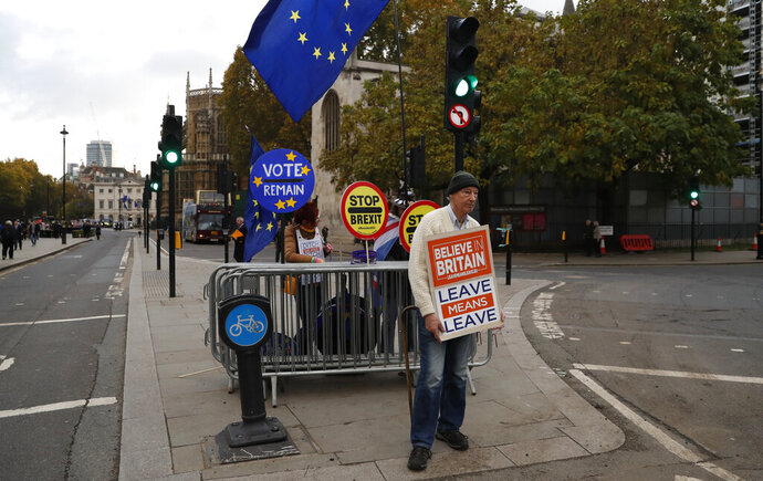 A pro-Brexit supporter demonstrates with anti-Brexit protesters behind him outside the Houses of Parliament on the final day of the lawmakers sitting before the start of the general election campaign in London, Tuesday, Nov. 5, 2019. Britain goes to the polls on Dec. 12. (AP Photo/Alastair Grant)