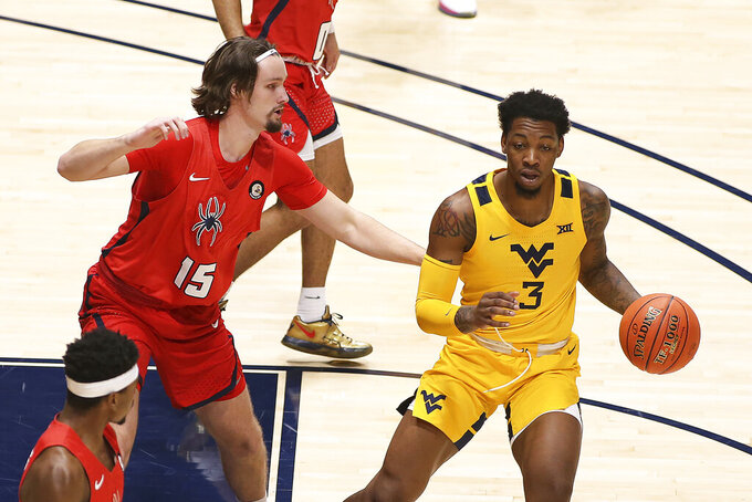West Virginia forward Gabe Osabuohien (3) is defended by Richmond forward Matt Grace (15) during the first half of an NCAA college basketball game Sunday, Dec. 13, 2020, in Morgantown, W.Va. (AP Photo/Kathleen Batten)