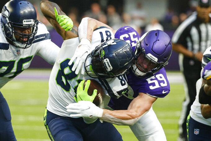 Minnesota Vikings outside linebacker Nick Vigil (59) tackles Seattle Seahawks tight end Gerald Everett (81) in the first half of an NFL football game in Minneapolis, Sunday, Sept. 26, 2021. (AP Photo/Bruce Kluckhohn)