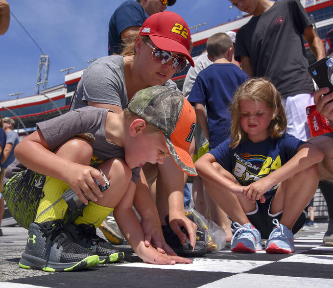 A family signs their names to the start/finish line during the fan track walk at Bristol Motor Speedway before the Bass Pro Shops NRA Night Race, Saturday, Aug, 17, 2019, in Bristol, Tenn. (Andre Teague/Bristol Herald Courier via AP)