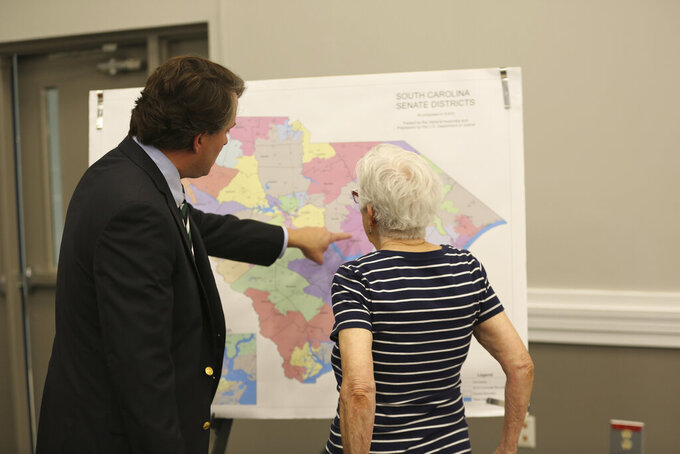 People look over the current South Carolina Senate districts at a public meeting by a Senate subcommittee on redistricting on Wednesday, July 28, 2021, in Sumter, S.C. Senators are holding 10 public hearings across the state. (AP Photo/Jeffrey Collins)