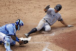 New York Yankees' Brett Gardner beats the tag by Kansas City Royals catcher Martin Maldonado to score on a sacrifice fly hit by Gio Urshela during the sixth inning of the first baseball game in a doubleheader, Saturday, May 25, 2019, in Kansas City, Mo. (AP Photo/Charlie Riedel)