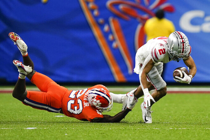 Ohio State wide receiver Chris Olave is tackled by Clemson cornerback Andrew Booth Jr. during the first half of the Sugar Bowl NCAA college football game Friday, Jan. 1, 2021, in New Orleans. (AP Photo/Gerald Herbert)
