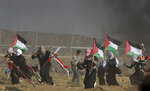 Female protesters wave Palestinian national flags as they run from teargas fired by Israeli troops, near fence of Gaza Strip border with Israel, during a protest east of Gaza City, Friday, Sept. 7, 2018. A teenager was killed and dozens of other Palestinians injured by Israeli fire at a border protest, Gaza officials said. (AP Photo/Adel Hana)