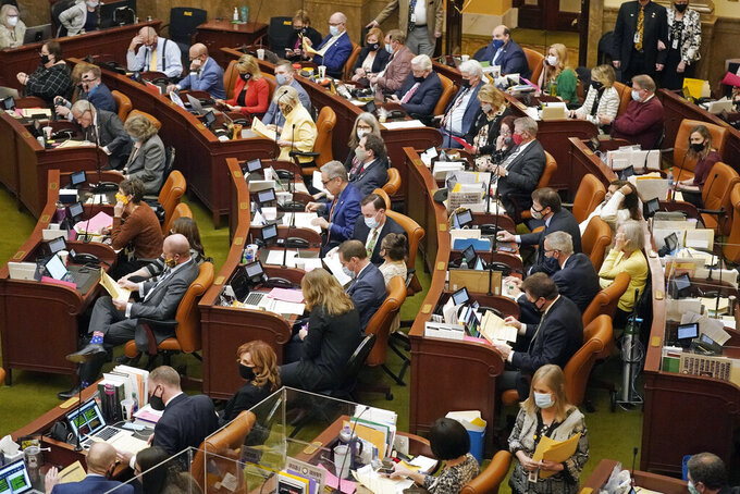 FILE - The Utah House of Representatives work on the House floor on March 5, 2021, in Salt Lake City. Utah lawmakers have voted to require every cellphone and tablet sold there to automatically block pornography, the conservative state's most recent move targeting online porn and one that critics call a significant intrusion on free speech. (AP Photo/Rick Bowmer, File)