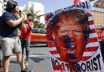 A protester shouts slogans with an image of U.S. President Donald Trump during a rally opposing the recent U.S. attack that killed Iranian Gen. Qassem Soleimani in Manila, Philippines Monday Jan. 6, 2020. Philippine President Rodrigo Duterte has ordered the military to prepare to deploy its aircraft and ships
