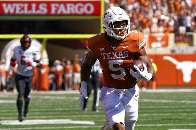 Texas running back Bijan Robinson (5) runs for a touchdown against Texas Tech during the first half of an NCAA college football game on Saturday, Sept. 25, 2021, in Austin, Texas. (AP Photo/Chuck Burton)